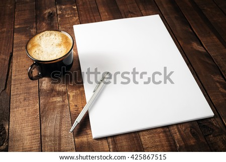 Blank branding template on vintage wooden table background. Letterhead, coffee cup and pen. Photo of blank stationery. Mock-up for design portfolios. - stock photo