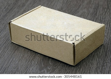 Blank brown box mock up on wood background - stock photo
