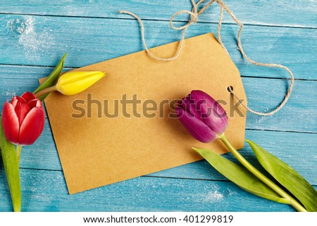 Blank brown gift tag or label with copy space for your greeting with fresh spring tulips on a rustic blue-green wooden table viewed close up from overhead - stock photo