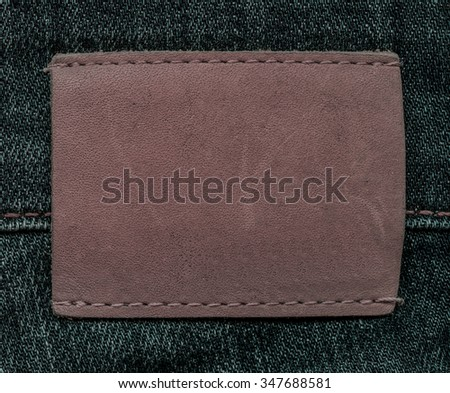 blank brown  leather label as place for Your text on jeans background