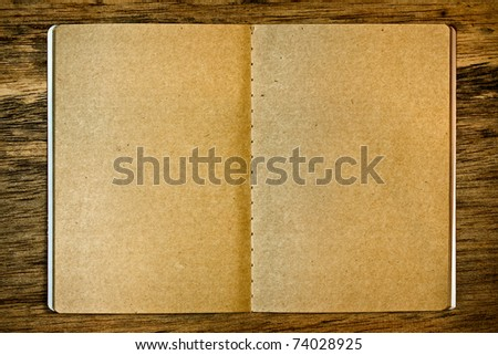 Blank brown notepad on the wood background