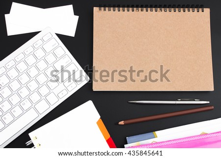 blank brown paper on black table / Open blank brown paper notebook with copy space and a pen lying on a black desk, view from above / for your text or message / top view - stock photo