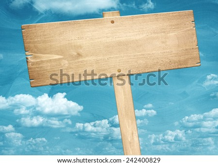 Blank brown wooden signpost against blue sky. - stock photo