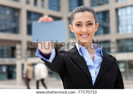 blank business card,  businesswoman with blank business card in a hand, office building as background