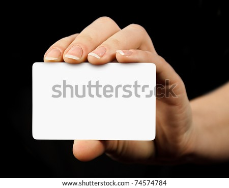 blank business card in a hand isolated on black - stock photo