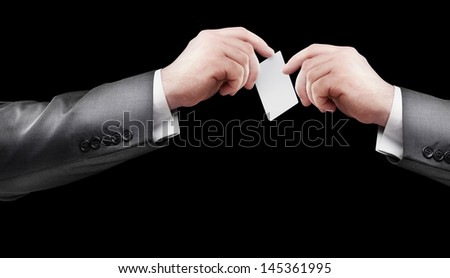 Blank business card in a hand Isolated on black background - stock photo