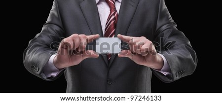 Blank business card in a hand Isolated on black background