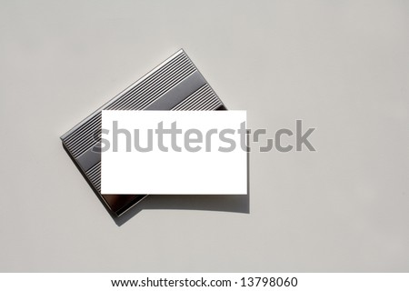 Blank business card - insert your own text - sitting on silver card holder with grey background which is perfect for copy space.