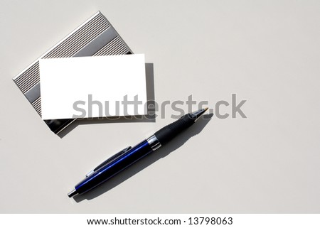 Blank business card - insert your own text - sitting on silver card holder with grey background which is perfect for copy space and pen.