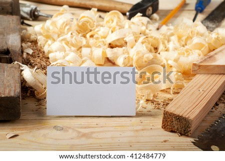 Blank business card on wooden table for carpenter tools with sawdust top view. - stock photo