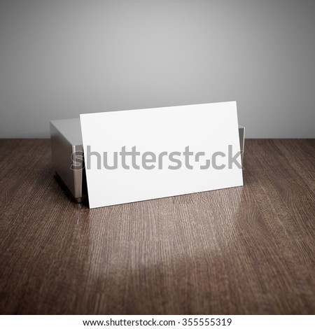 Blank business card with aluminum holder on wooden table - stock photo