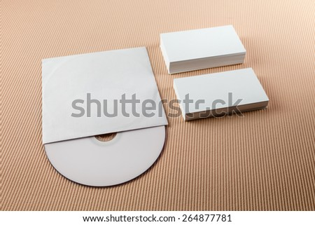 Blank business cards and CD on a beige striped background. Template for branding identity. Shallow depth of field. - stock photo
