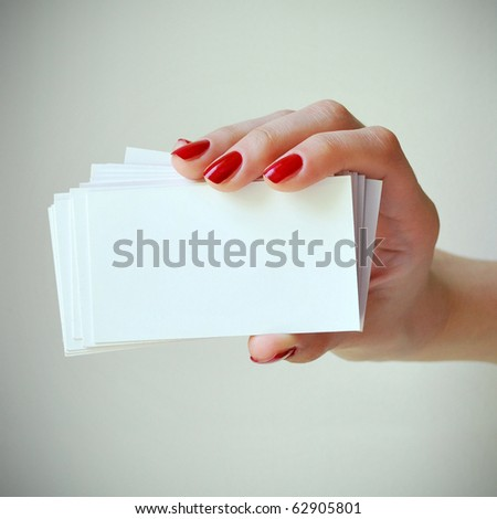 Blank business cards in elegant female hand with red nails - stock photo