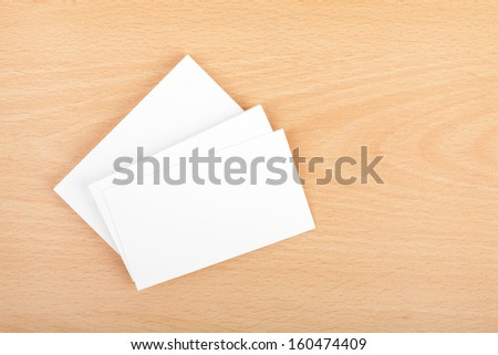 Blank business cards on wooden office table - stock photo