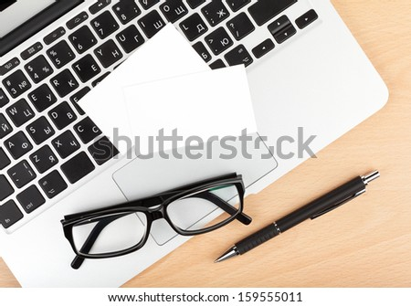 Blank business cards over laptop on wooden office table - stock photo