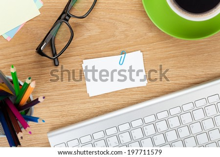 Blank business cards over office table with supplies - stock photo