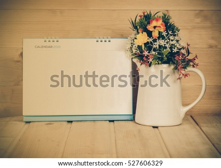 Blank calendar with vase on wood table with yellow light tone
