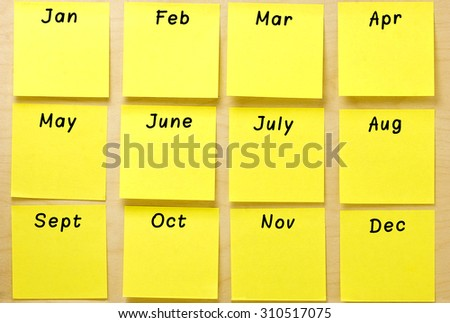 Blank calendar yellow postit notes affixed on a wooden board - stock photo