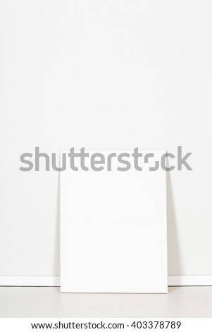 Blank canvas leaning against empty white wall - stock photo