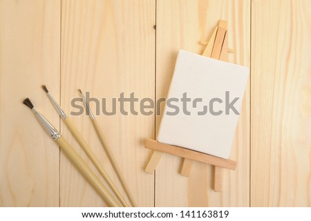 Blank canvas on easel on wooden desktop - stock photo