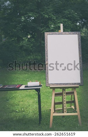 blank canvas rests on a easel, retro stylized - stock photo
