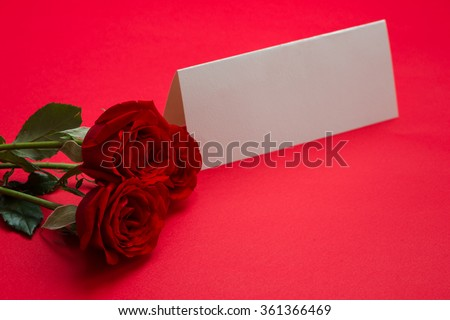 Blank card and a bouquet of red roses on red background, Valentines Day background. Red rose and paper Valentines Day
