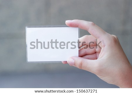 Blank card in a woman's hand, close up