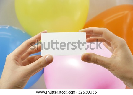 blank card in hands of the women on background colour balls
