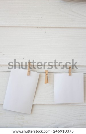 Blank card on white wall background and wood clip - stock photo