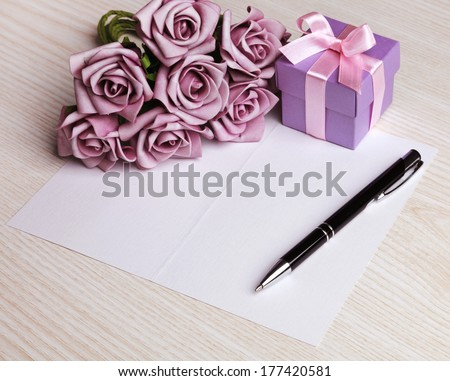 blank card with a pen, purple roses and purple gift box - stock photo