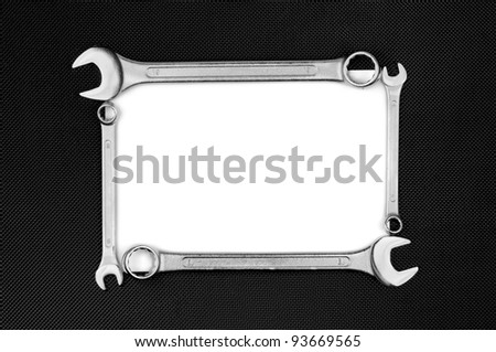 Blank card with wrenches on the black dotted metal plate. - stock photo