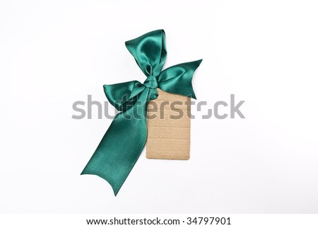 Blank cardboard gift tag tied with a bow of green satin ribbon