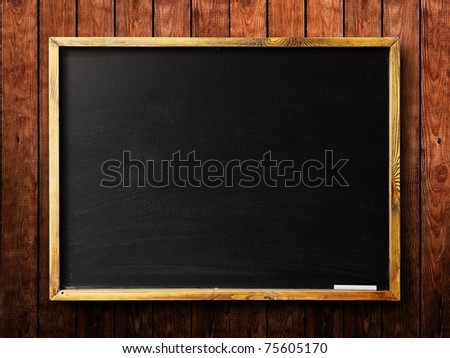 Blank chalkboard in wooden frame on wooden wall - stock photo