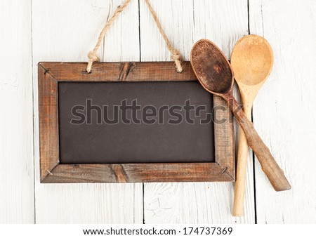 Blank chalkboard sign with wood cooking spoons - stock photo