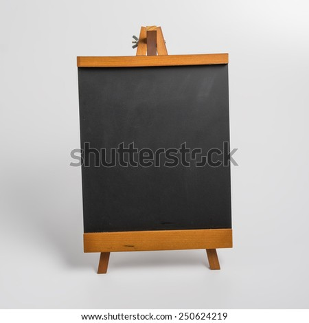 Blank chalkboard with wooden stand with low light. - stock photo