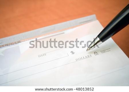 Blank check, checkbook and pen as a financial concept - stock photo