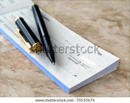 Blank cheque with pen on the table - stock photo