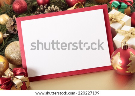 Blank Christmas card or invitation with red envelope surrounded by decorations. Space for copy. - stock photo