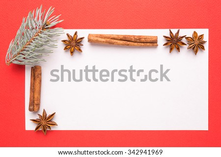 blank christmas card with anise star and cinnamon on red background - stock photo