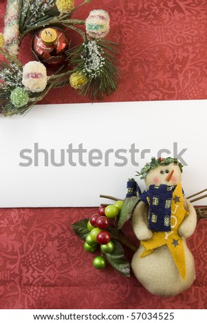 blank Christmas card with snowman, berry accent, frosted foliage, red bauble and copyspace - stock photo