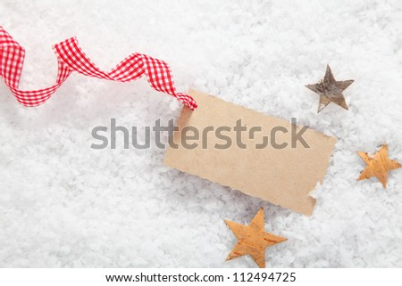 Blank Christmas gift label with a decorative red and white checked rustic ribbon surrounded by stars on fresh winter snow - stock photo
