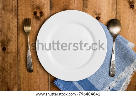 Blank clean white plate with fork, spoon, napkin on dark wooden background. Food invitation. Ready to serve and cook fresh meal. Good for using with text and signs.