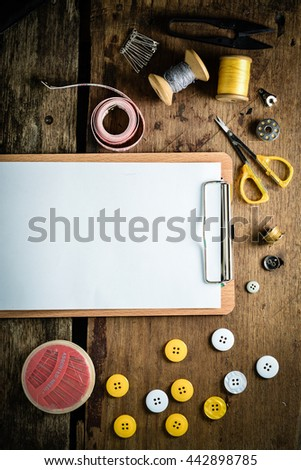 Blank clipboard and Sewing tools kit on wooden textured background
