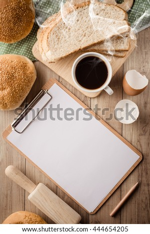 Blank clipboard with bread, coffee and kitchen utensils on wooden background