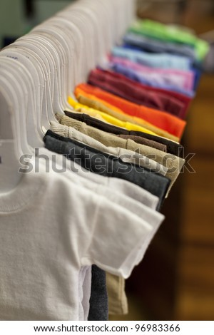 Blank colorful kids shirts hanging in a row in a shop. - stock photo