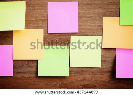 Blank colorful sticky paper note attach on wood wall background. - stock photo
