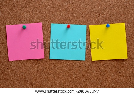 Blank, colourful notes pinned into brown corkboard - stock photo