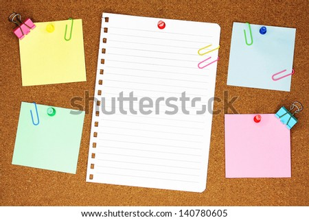 Blank, colourful notes pinned into brown corkboard with paper clips.  - stock photo