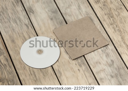 Blank compact disk and cover on wood background - stock photo