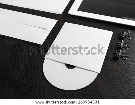 Blank compact disk on wooden table. Fragment of blank stationery and corporate identity template on dark background. Template for branding identity for designers. Shallow depth of field. - stock photo